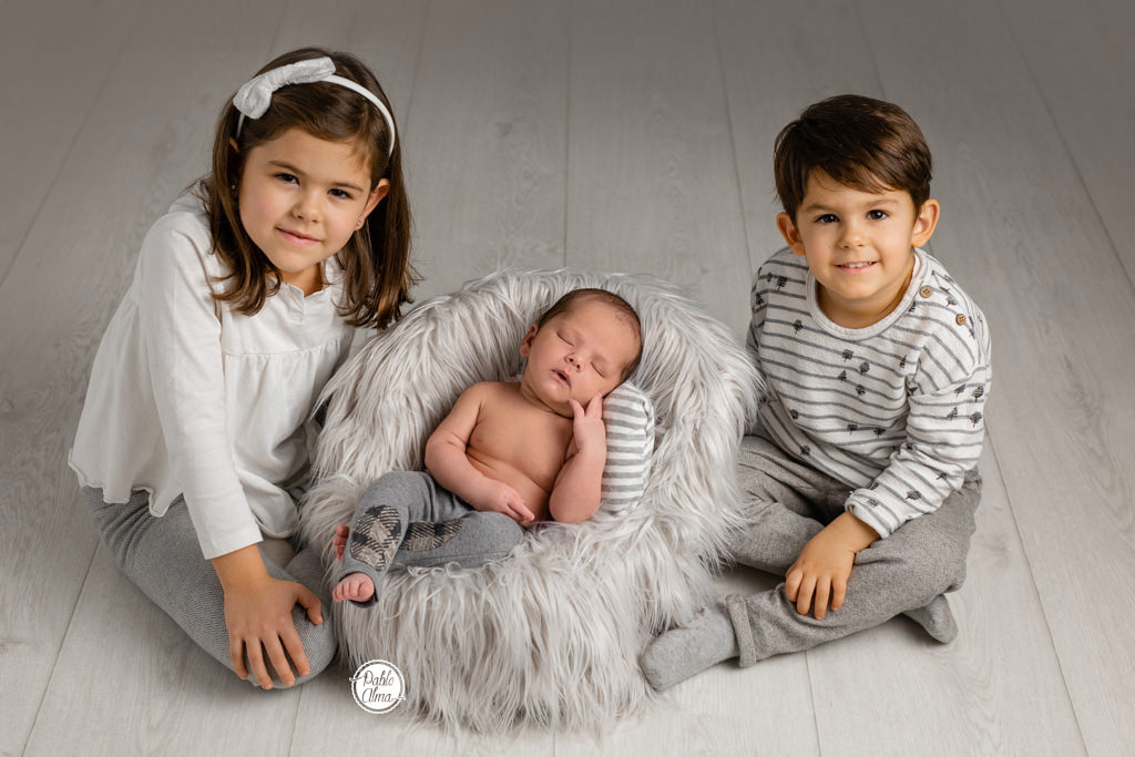 Bebé recién nacido con sus dos hermanos