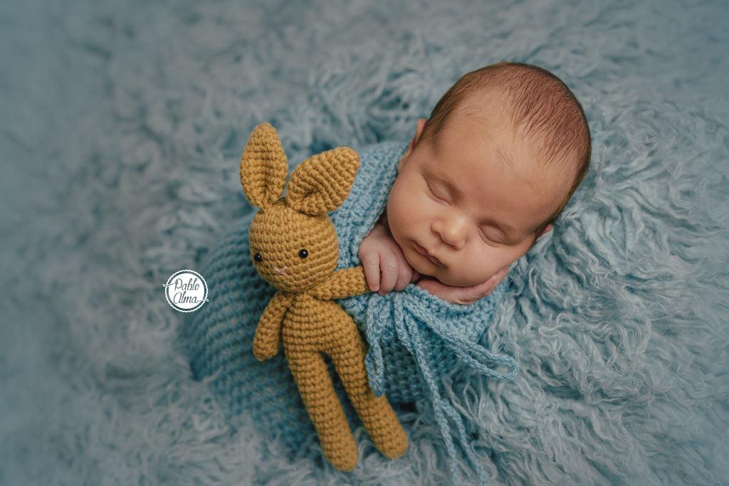 Recién nacido con muñeco en puf y flokati - Envoltura