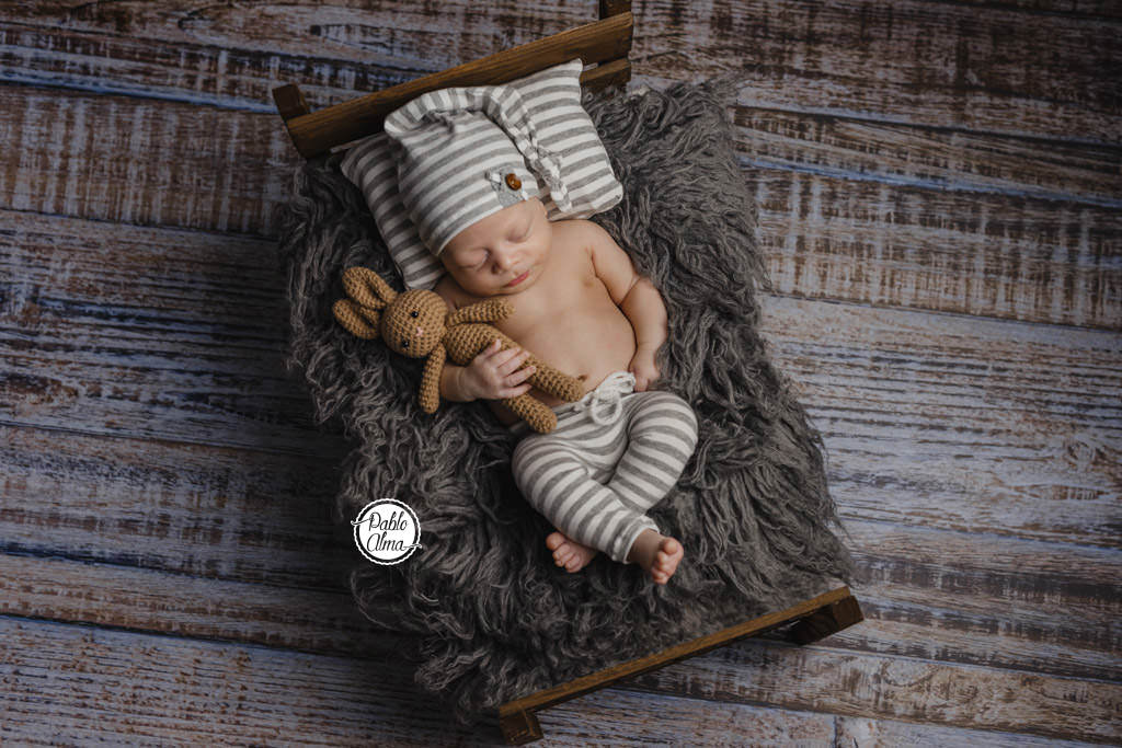 Bebé recién nacido en camita durmiendo