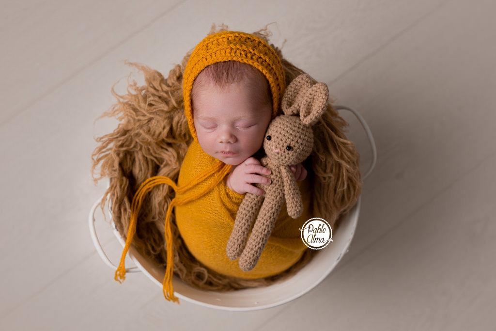 Foto de recién nacido con envoltura en cubito