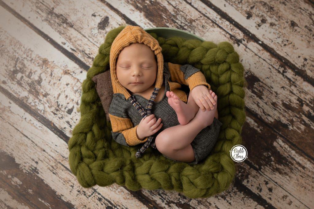 Bebé recién nacido en cubito boca arriba con sudadera y capucha